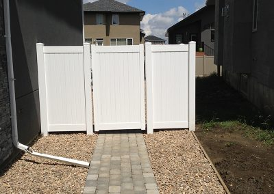 pvc fence with stone landscaping and gate